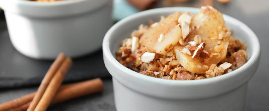 Ramekin with apple crisp on table, closeup
